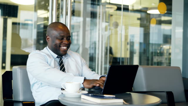 Successful african american businessman using laptop computer receiving good message and become very excited and dancing while sitting in modern cafe duiring coffee braek